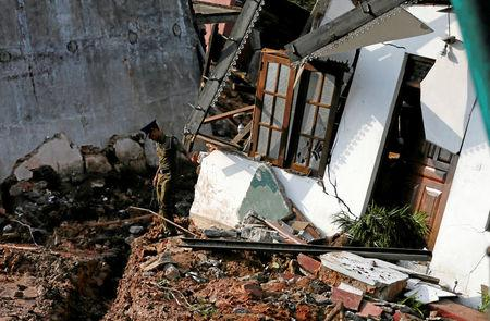A police officer inspects a damaged house for victims during a rescue mission after a garabage dump collapsed and buried dozens of houses in Colombo