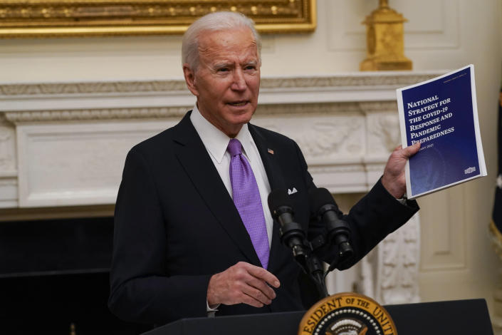 FILE - In this Jan. 21, 2021, file photo President Joe Biden holds a booklet as he speaks about the coronavirus in the State Dinning Room of the White House in Washington. (AP Photo/Alex Brandon, File)