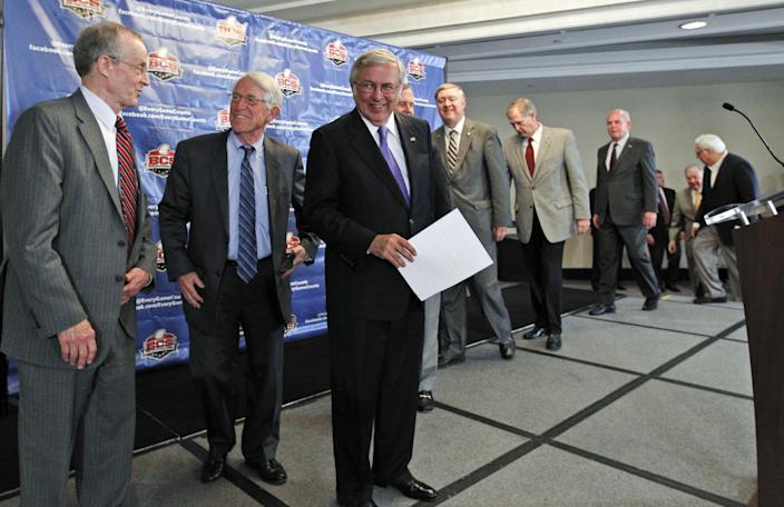 Virginia Tech President Charles Steger, third from left, smiles as he and others arrive for a media availability after a BCS presidential oversight committee meeting, Tuesday, June 26, 2012, in Washington. A committee of university presidents on Tuesday approved the BCS commissioners' plan for a four-team playoff to start in the 2014 season. (AP Photo/Alex Brandon)