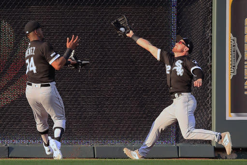 Chicago White Sox center fielder Charlie Tilson, right, catches a fly ball hit by Kansas City Royals' Whit Merrifield during the first inning of a baseball game at Kauffman Stadium in Kansas City, Mo., Tuesday, July 16, 2019. Chicago White Sox left fielder Eloy Jimenez (74) backs up and was injured on the play. (AP Photo/Orlin Wagner)