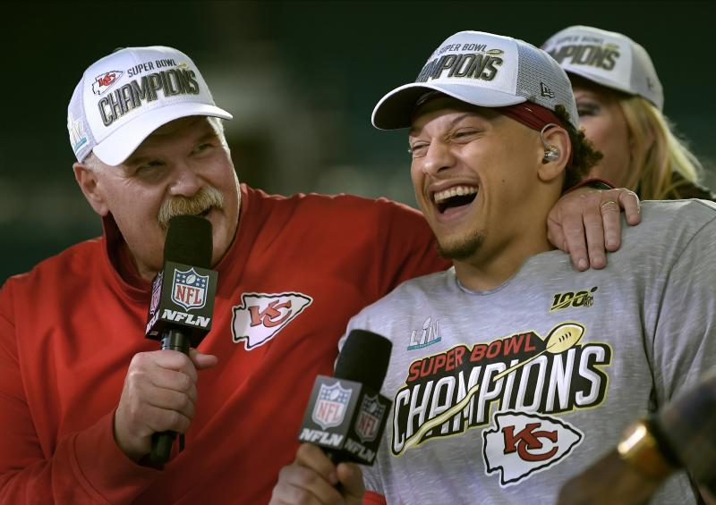 Andy Reid and Patrick Mahomes laugh while wearing Super Bowl champion gear after winning the Super Bowl.