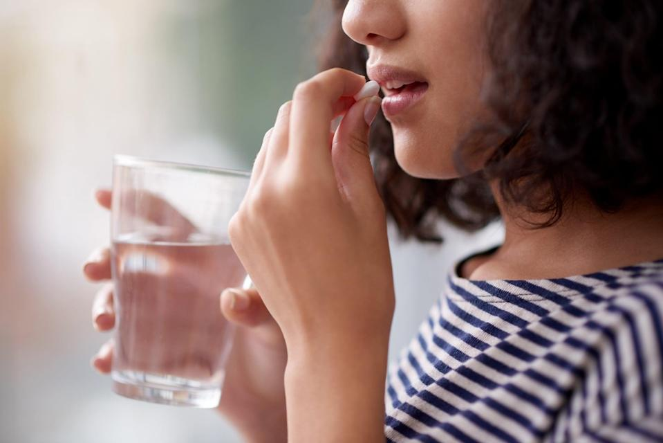 Cropped shot of an unrecognizable teenage girl drinking medication