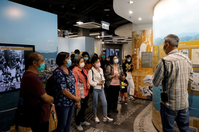 FILE PHOTO: Tourists wearing face masks listen to an instructor inside Hong Kong News-Expo during a Hong Kong Tourism Board's free local tour, following the coronavirus disease (COVID-19) outbreak, in Hong Kong