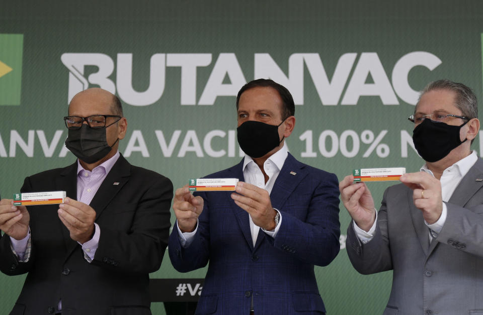 (L-R) Butantan Institute director Dimas Covas, Sao Paulo Governor Joao Doria and Sao Paulo Health Secretary Jean Gorinchteyn, pose with ButanVac vaccines candidate against Covid-19, at the Butantan Institute, in Sao Paulo, Brazil, on March 26, 2021. - The Brazilian ButanVac vaccine will ask for authorization from the National Health Surveillance Agency (Anvisa) to start clinical trials of phases 1 and 2 in humans, involving 1,8 thousand volunteers. Research started on March 26, 2020 and the production goal is to start on May and to deliver 40 million doses starting on July, 2021. (Photo by Miguel Schincariol / AFP) (Photo by MIGUEL SCHINCARIOL/AFP via Getty Images)