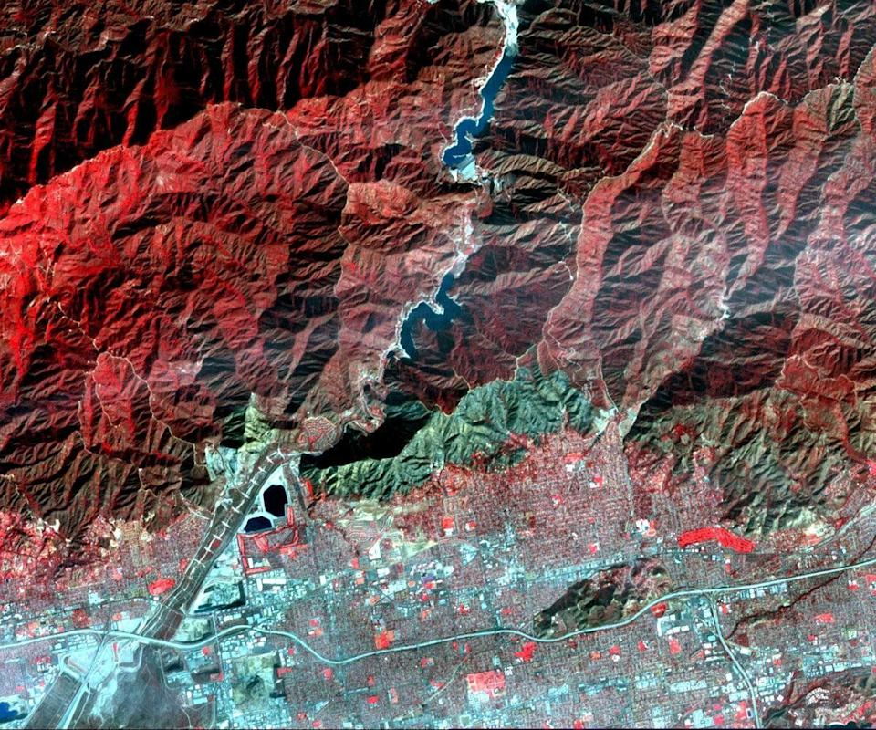 On Jan. 16, 2014, a wildfire broke out in the mountains above the Los Angeles suburbs of Glendora and Azusa. The fire consumed almost 2,000 acres and destroyed several homes, after starting from an illegal campfire. This image, acquired Jan. 23, 2014 from the ASTER instrument on NASA's Terra spacecraft, depicts vegetation in shades of red. The burned area is seen as the blue-gray area at the base of the mountains.