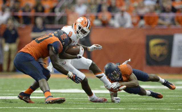 """Clemson wide receiver <a class=""""link rapid-noclick-resp"""" href=""""/ncaaf/players/252164/"""" data-ylk=""""slk:Deon Cain"""">Deon Cain</a> (8) is tackled by Syracuse linebacker Parris Bennett (30) and defensive back <a class=""""link rapid-noclick-resp"""" href=""""/ncaaf/players/256871/"""" data-ylk=""""slk:Christopher Fredrick"""">Christopher Fredrick</a> (3) during the first half of an NCAA college football game, Friday, Oct. 13, 2017, in Syracuse, N.Y. (AP Photo/Adrian Kraus)"""