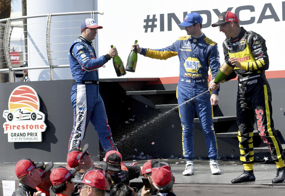Sebastien Bourdais (18), right, celebrates after winning the IndyCar Firestone Grand Prix of St. Petersburg Sunday, March 11, 2018, in St. Petersburg, Fla. Graham Rahal (15), left, finished second and Alexander Rossi (27) finished third. (AP Photo/Jason Behnken)