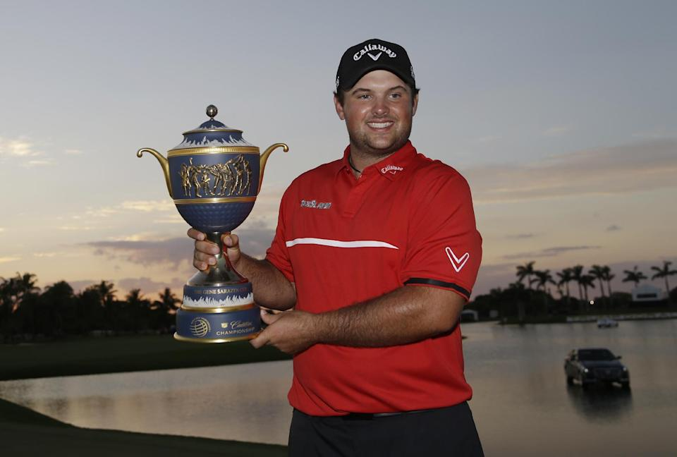 Patrick Reed holds The Gene Sarazen Cup after winning the Cadillac Championship golf tournament Sunday, March 9, 2014, in Doral, Fla. (AP Photo/Wilfredo Lee)
