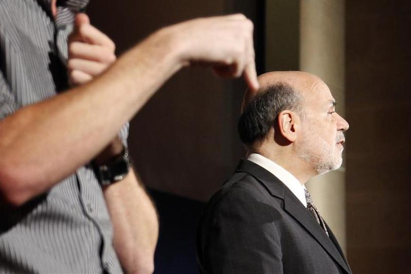 A sign language interpreter translates remarks by U.S. Federal Reserve Chairman Ben Bernanke (R) at the National Economists Club annual dinner at the U.S. Chamber of Commerce in Washington, November 19, 2013.