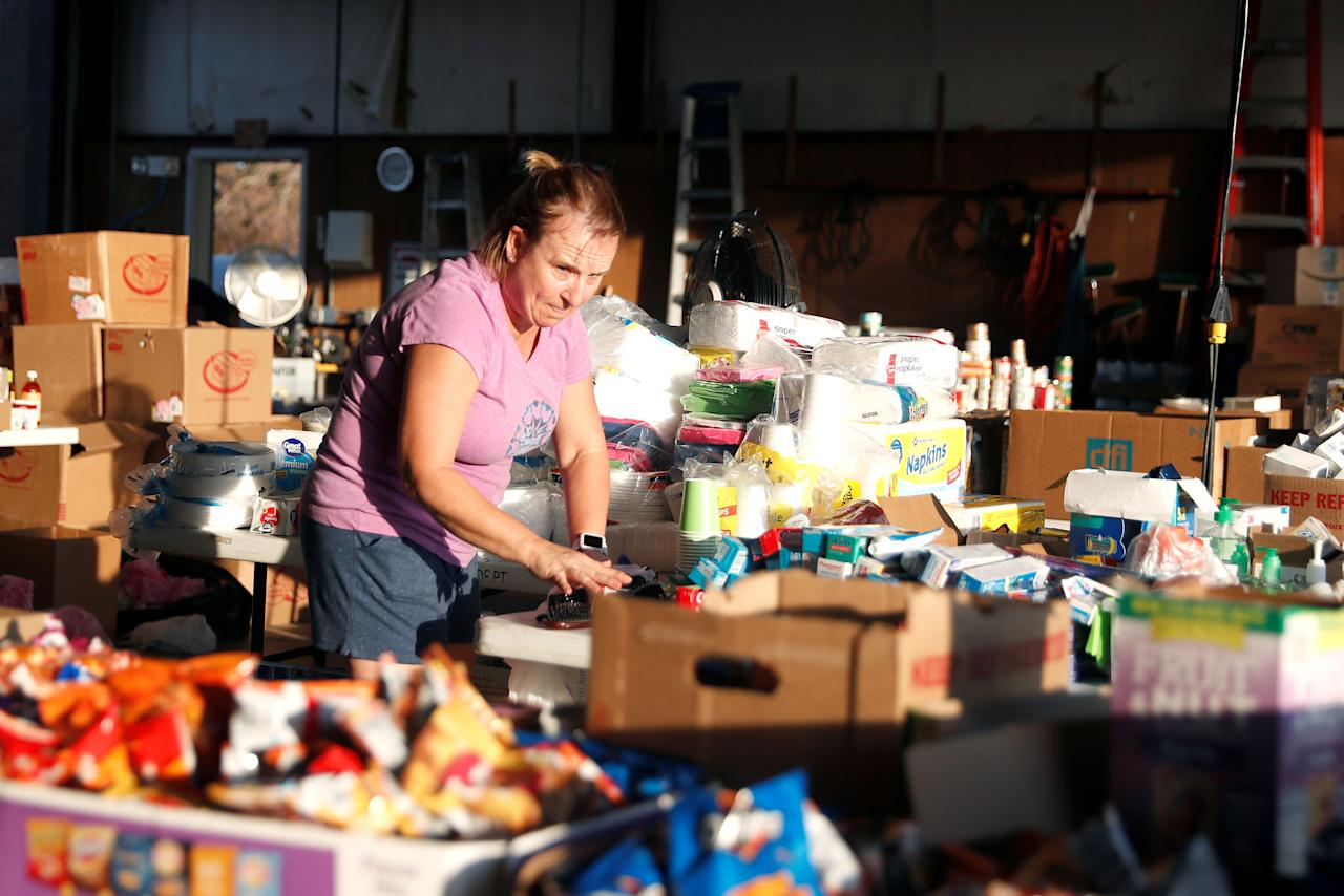 <p>Tonya Plair, 50, sorts emergency goods being distributed in the Gulf County Beaches Fire Station, which is also used as a polling place, in the aftermath of Hurricane Michael in Port Saint Joe, Fla., Oct. 17, 2018. (Photo: Terray Sylvester/Reuters) </p>