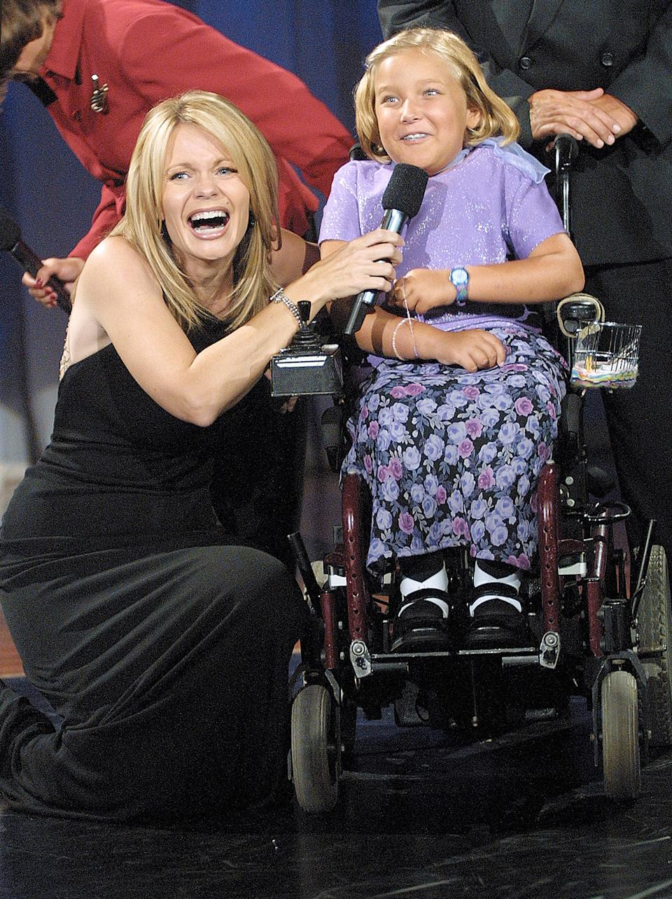 "Telethon co-host Jann Carl spoke with Sarah Schweger, 8, during the 2001 Jerry Lewis MDA Telethon in Los Angeles. Activist Karly Joy, a critic of the telethon, recently called scenes like this one part of a ""huge pity party."" (Photo: Frederick M. Brown/Getty Images)"