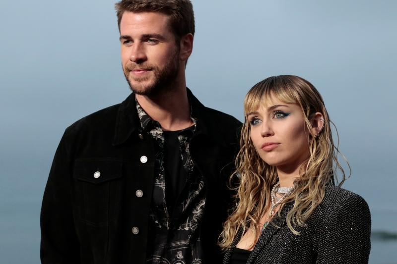 US singer Miley Cyrus and husband Australian actor Liam Hemsworth arrive for the Saint Laurent Men's Spring-Summer 2020 runway show in Malibu, California, on June 6, 2019. (Photo by Kyle GRILLOT / AFP) (Photo credit should read KYLE GRILLOT/AFP via Getty Images)