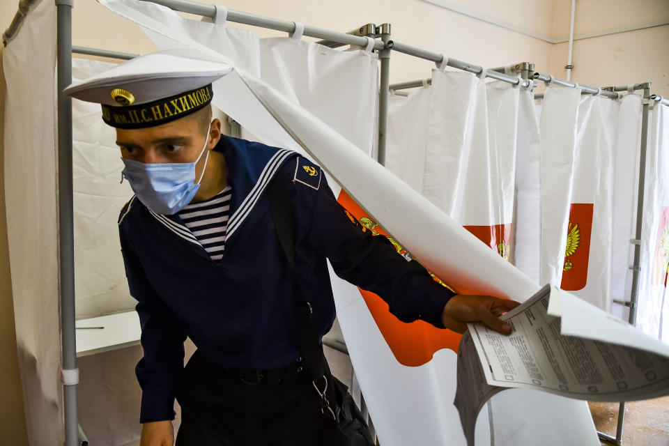 A Russian military sailor leaves a voting booth at a polling station during the Parliamentary elections in Sevastopol, Crimea, Sunday, Sept. 19, 2021. The head of Russia's Communist Party, the country's second-largest political party, is alleging widespread violations in the election for a new national parliament in which his party is widely expected to gain seats. (AP Photo)