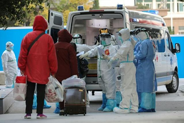 A medical staffer checks information as patients infected by the novel coronavirus leave the Wuhan No.3 Hospital in March 2020 (AFP Photo/STR)