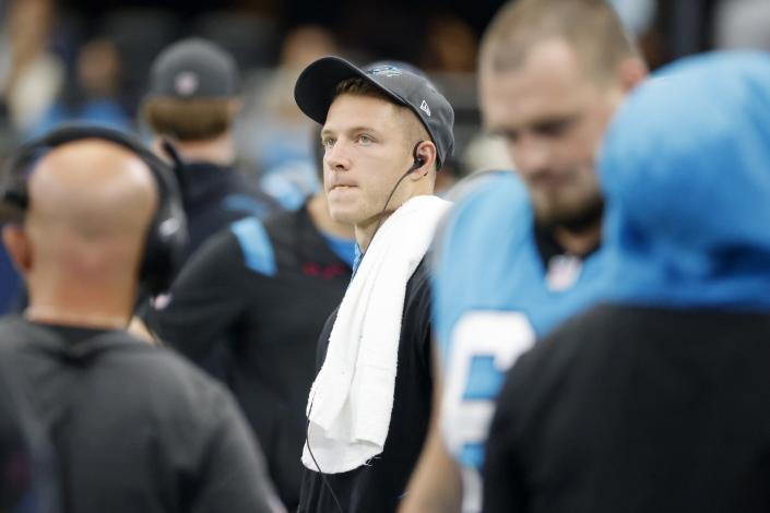 Carolina Panthers running back Christian McCaffrey watches play from the sideline against the Dallas Cowboys in the first half of a NFL football game in Arlington, Texas, Sunday, Oct. 3, 2021. (AP Photo/Michael Ainsworth)