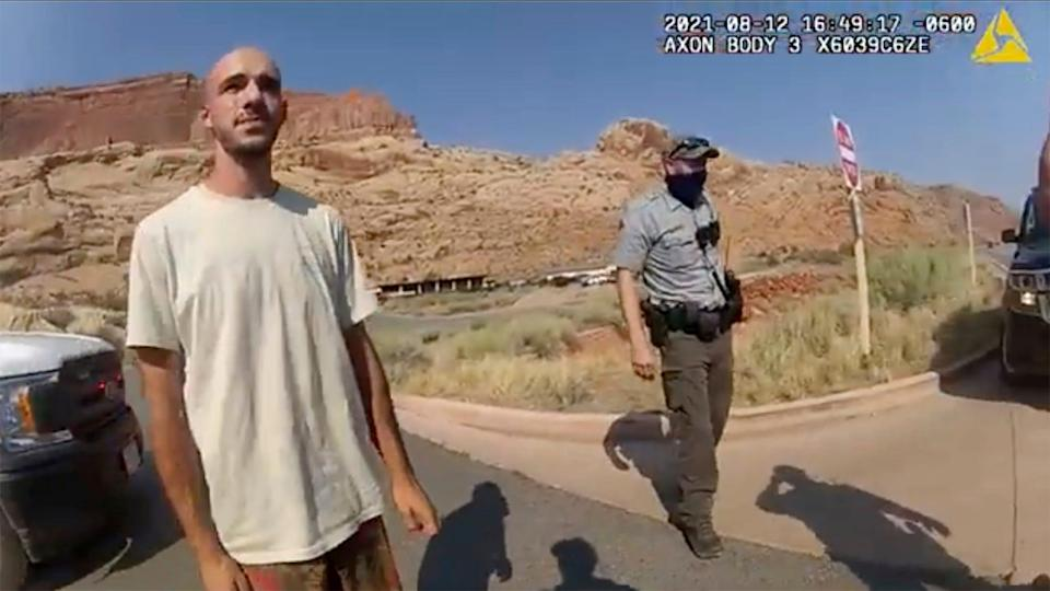 """This Aug. 12, 2021, photo from video provided by The Moab Police Department shows Brian Laundrie talking to a police officer after police pulled over the van he was traveling in with his girlfriend, Gabrielle """"Gabby"""" Petito, near the entrance to Arches National Park."""