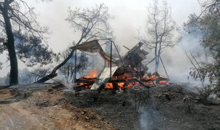 A wildfire fanned by strong winds rages near the Mediterranean coastal town of Manavgat, Antalya, Turkey, Wednesday, July 28, 2021. Authorities evacuated homes in Manavgat as a wildfire raged Wednesday through a forest. Gendarmerie forces helped move residents out of four neighborhoods in the town out of the fire's path as firefighters worked to control the blaze, the Manavgat district governor Mustafa Yigit told the state-run Anadolu Agency. (Arif Kaplan/IHA via AP)