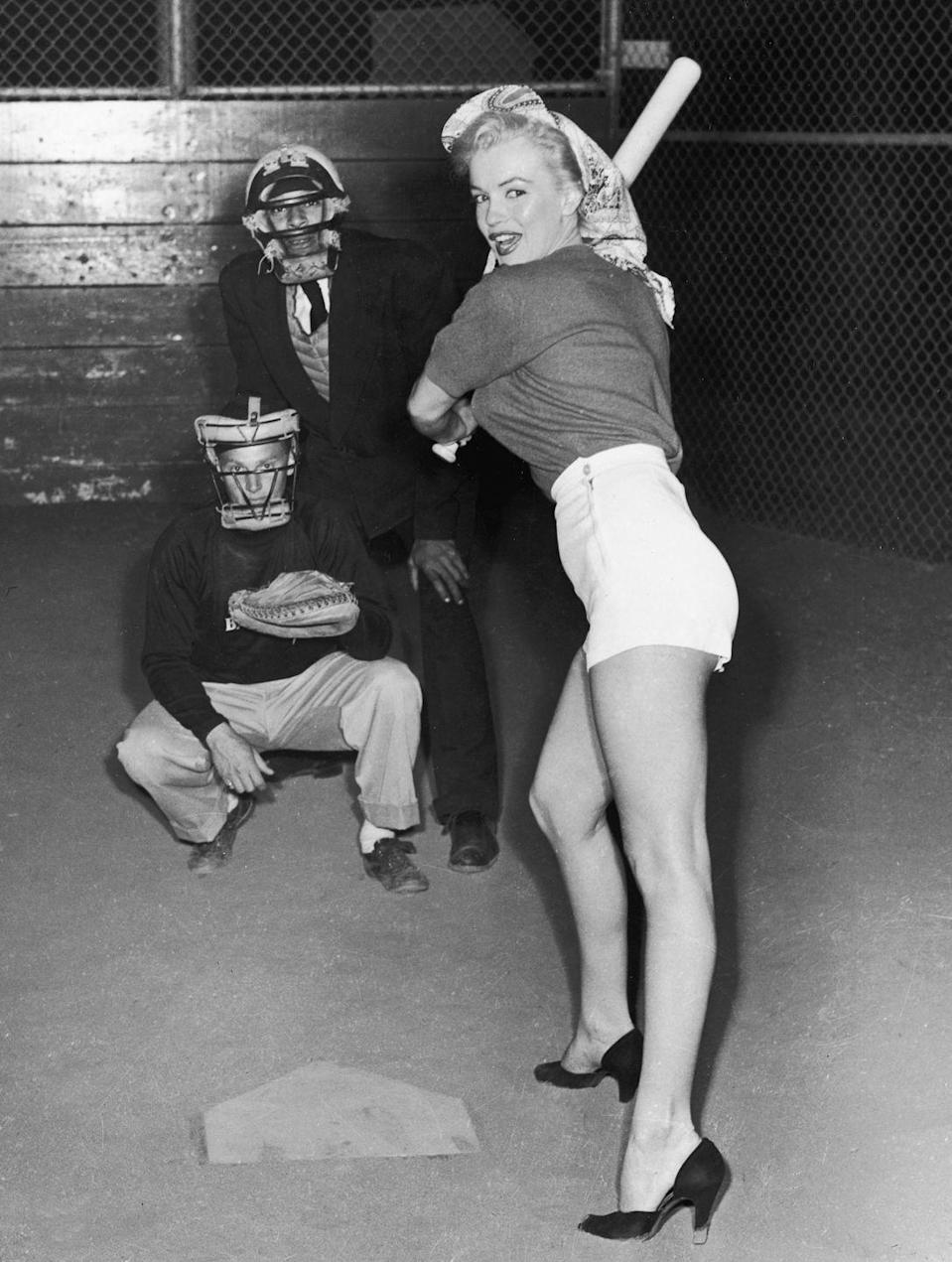 <p>Marilyn Monroe takes a swing at baseball during a 20th Century Fox studio league game, July 1, 1952.</p>