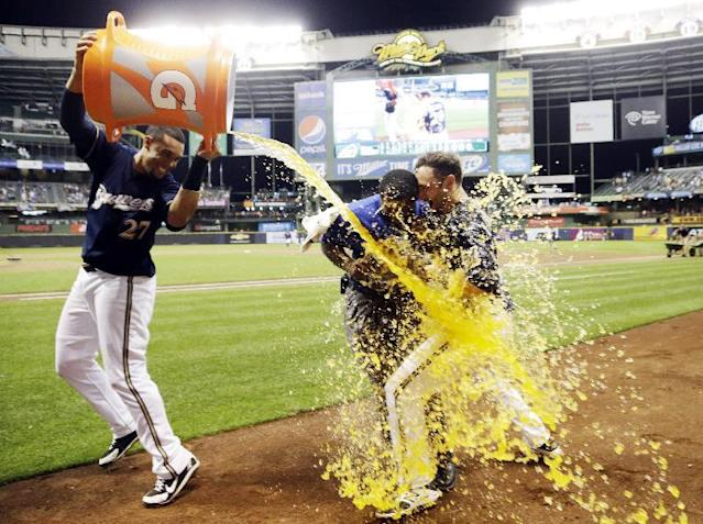 Milwaukee Brewers' Carlos Gomez dunks teammate Jonathan Lucroy during an interview after Lucroy hit a walk off home run during the ninth inning of a baseball game against the Cincinnati Reds Tuesday, July 22, 2014, in Milwaukee. The Brewers won 4-3. (AP Photo/Morry Gash)