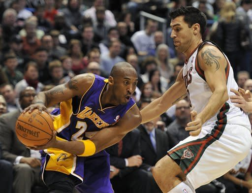 Los Angeles Lakers' Kobe Bryant drives to the basket against the Milwaukee Bucks' Carlos Delfino during the first half of an NBA basketball game on Saturday, Jan. 28, 2012, in Milwaukee. (AP Photo/Jim Prisching)