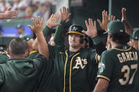Oakland Athletics catcher Sean Murphy is congratulated by teammates in the dugout after scoring a run in the third inning against the Texas Rangers in a baseball game Tuesday, June 22, 2021, in Arlington, Texas. (AP Photo/Louis DeLuca)