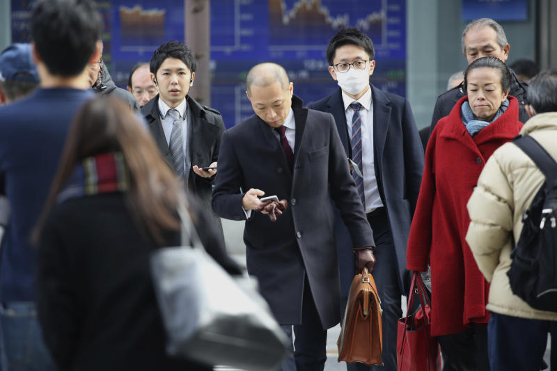 People walk by an electronic stock board of a securities firm in Tokyo, Monday, Dec. 9, 2019. Japan's economy grew at an annual rate of 1.8% in July-September, according to revised government data, better than the modest annual pace of 0.2% it gave as an earlier estimate.   (AP Photo/Koji Sasahara)