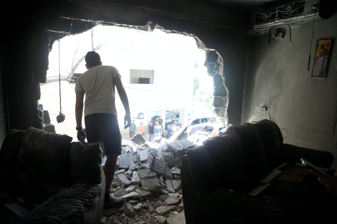 A man stands atop rubble as he surveys the damage after a rocket launched overnight from the Gaza Strip hit a residential building in Petah Tikva, Israel. (Reuters/Nir Elias)