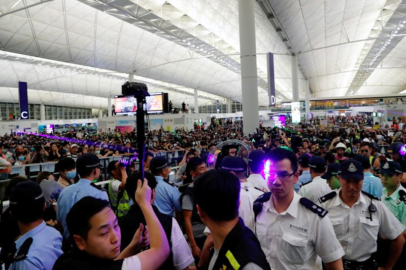 Police are pointed at with laser beams by anti-extradition bill protesters during a mass demonstration at the Hong Kong international airport, in Hong Kong, China, August 13, 2019. REUTERS/Tyrone Siu
