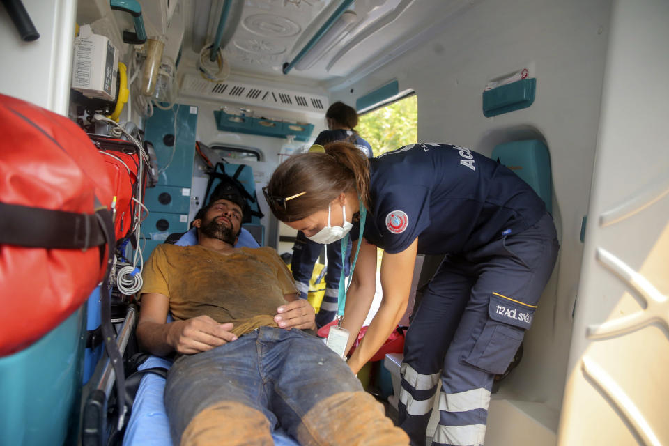 A nurse treats an exhausted Turkish volunteer as they fight wildfires in Turgut village, near tourist resort of Marmaris, Mugla, Turkey, Wednesday, Aug. 4, 2021. As Turkish fire crews pressed ahead Tuesday with their weeklong battle against blazes tearing through forests and villages on the country's southern coast, President Recep Tayyip Erdogan's government faced increased criticism over its apparent poor response and inadequate preparedness for large-scale wildfires.(AP Photo/Emre Tazegul)