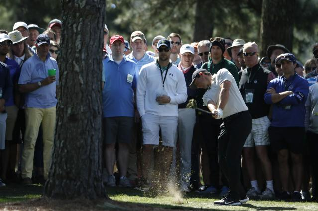 Rory McIlroy of Northern Ireland hits on by the crowd and a tree on the first fairway during second round play of the 2018 Masters golf tournament at the Augusta National Golf Club in Augusta, Georgia, U.S., April 6, 2018. REUTERS/Jonathan Ernst