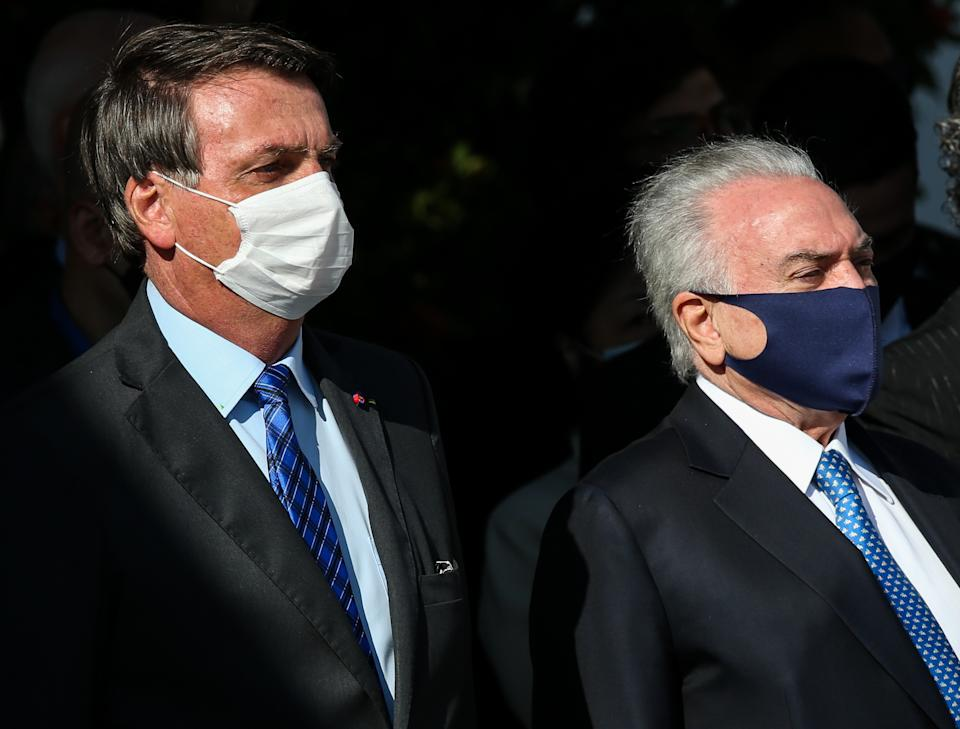 SAO PAULO, BRAZIL - AUGUST 12: President of Brazil Jair Bolsonaro and Brazil's former President Michel Temer look on during a visit to BASP (Sao Paulo Air Base) to accompany the Brazilian delegation's departure to Lebanon on August 12, 2020 in Sao Paulo, Brazil. Last week, an explosion in the port area of Beirut, the capital of Lebanon, left at least 160 dead and thousands injured. The delegation's mission is to deliver food, medicine and hospital supplies, including 100,000 surgical masks and mechanical respirators. (Photo by Alexandre Schneider/Getty Images)