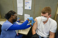 FILE - A registered nurse gives James Mullen the second dose of the coronavirus vaccine at a COVID-19 vaccination site at NYC Health + Hospitals Metropolitan, Thursday, Feb. 18, 2021, in New York. After months of coaxing people to get vaccinated against COVID-19 with incentives like museum tickets and transit passes, New York City is sweetening the pot by offering $100 to any city resident who gets a first dose of a coronavirus vaccine at a city-run site, Mayor Bill de Blasio said Wednesday, July 28, 2021. (AP Photo/Mary Altaffer, File)