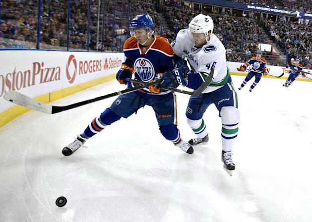 Vancouver Canucks' Nicklas Jensen (46) and Edmonton Oilers' Martin Marincin (85) battle for the puck during first period NHL hockey action in Edmonton, Alta., on Saturday April 12, 2014. (AP Photo/The Canadian Press, Jason Franson)