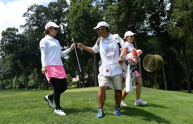 Mika Miyazato, left, and Mamiko Higa, right, both of Japan, celebrate a birdie with their caddie on the first hole during the third round of the International Crown golf tournament on Saturday, July 26, 2014, in Owings Mills, Md. (AP Photo/Gail Burton)