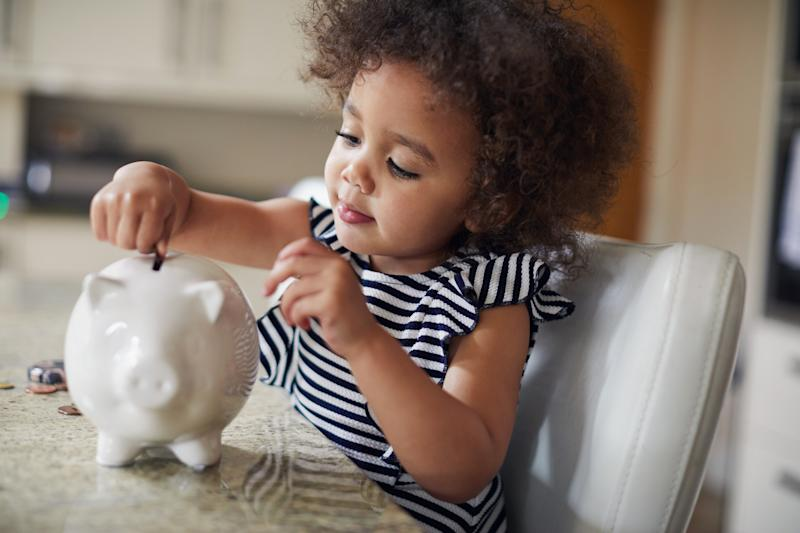 Little toddler girl saving money in her piggy bank