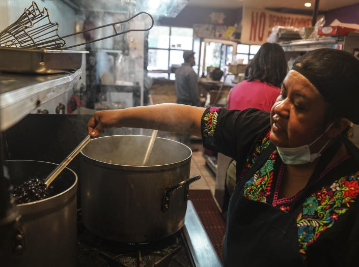 Natalia Méndez cooks in the kitchen of La Morada, an award-winning Mexican restaurant she co-owns with her family in South Bronx in New York. After recovering from COVID-19 symptoms, the family raised funds to reopen the restaurant, which they also turned into a soup kitchen serving 650 meals daily. (AP Photo/Bebeto Matthews)