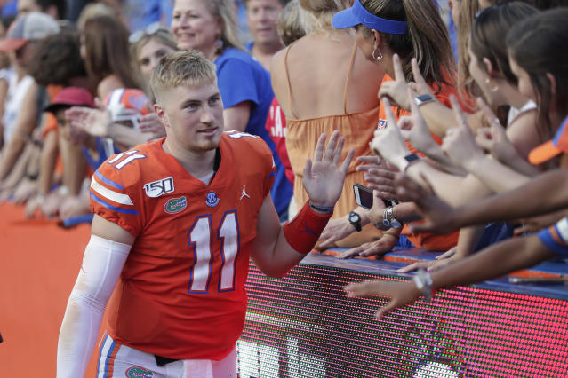 "Florida quarterback <a class=""link rapid-noclick-resp"" href=""/ncaaf/players/263160/"" data-ylk=""slk:Kyle Trask"">Kyle Trask</a> (11) high fives fans after defeating Towson in an NCAA college football game, Saturday, Sept. 28, 2019, in Gainesville, Fla. (AP Photo/John Raoux)"