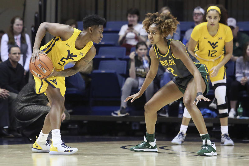 West Virginia guard Tynice Martin (5) looks to pass the ball while defended by Baylor guard DiDi Richards (2) during the first half of an NCAA college basketball game Monday, Feb. 24, 2020, in Morgantown, W.Va. (AP Photo/Kathleen Batten)