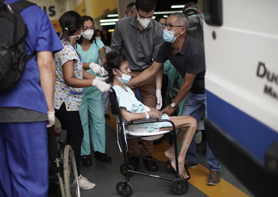 A patient is evacuated from the Bonsucesso Federal Hospital, which has a COVID-19 unit, while firefighters douse a fire in Rio de Janeiro, Brazil, Tuesday, Oct. 27, 2020. According to the fire department, there were no casualties. (AP Photo/Silvia Izquierdo)
