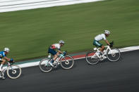Simon Philip Yates of Great Britain, center, is seen in this slow shutter speed photo, comptes during the men's cycling road race at the 2020 Summer Olympics, Saturday, July 24, 2021, in Oyama, Japan. (AP Photo/Thibault Camus)