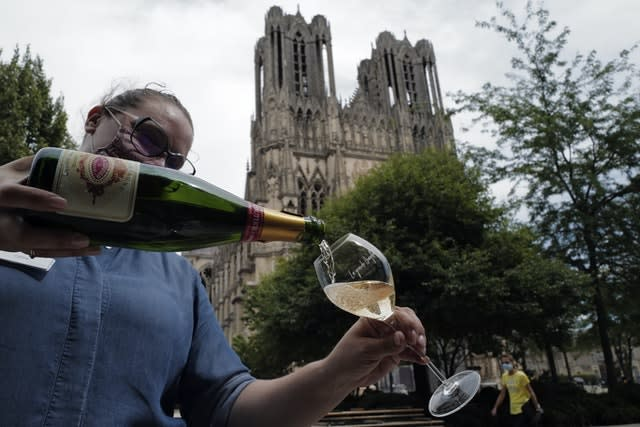 A waitress serves a glass of champagne at La Grande Georgette restaurant in front of the cathedral in Reims, in the Champagne region (Francois Mori/AP)