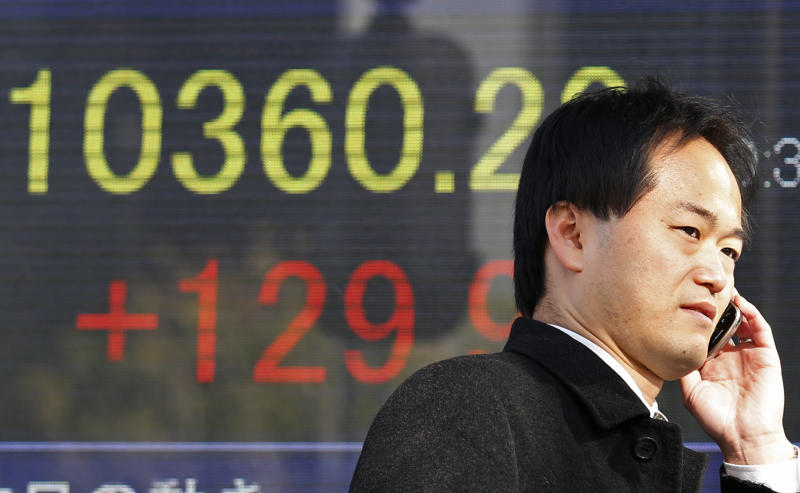A businessman walks by an electronic stock board of a securities firm in Tokyo, Thursday, Dec. 27, 2012. Asian markets have risen amid optimism that Japan's new leaders will stimulate its sluggish economy. (AP Photo/Koji Sasahara)