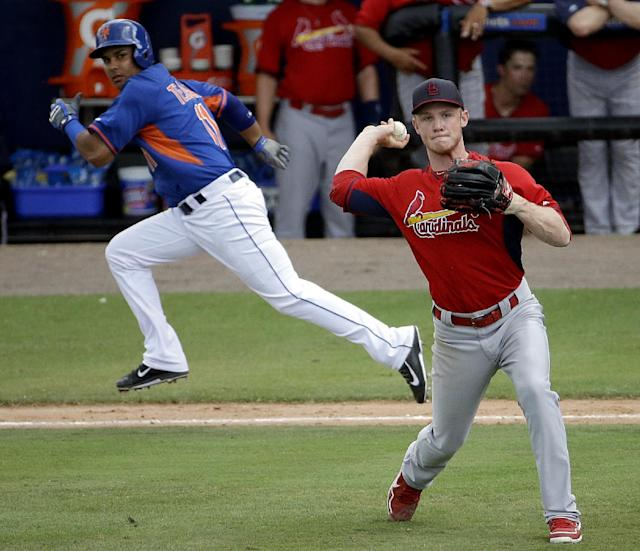 St. Louis Cardinals relief pitcher Keith Butler, right, throws to third base to get out New York Mets' Taylor Teagarden after fielding a bunt by Ruben Tejada, left, in the seventh inning of an exhibition spring training baseball game, Wednesday, March 12, 2014, in Port St. Lucie, Fla. (AP Photo/David Goldman)