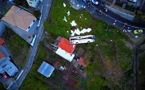 A video grab obtained from drone footage shows the wreckage of a tourist bus that crashed in Canico, on the Portuguese island of Madeira - Credit: AFP