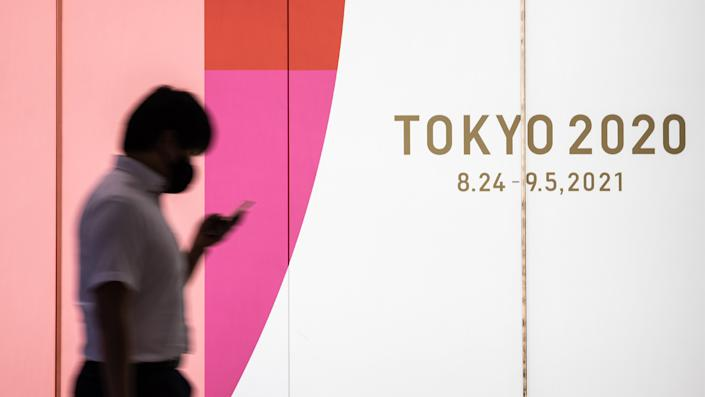 A man wearing a face mask walks past a display promoting Tokyo 2020 on July 14, 2021 in Tokyo, Japan. (Takashi Aoyama/Getty Images)