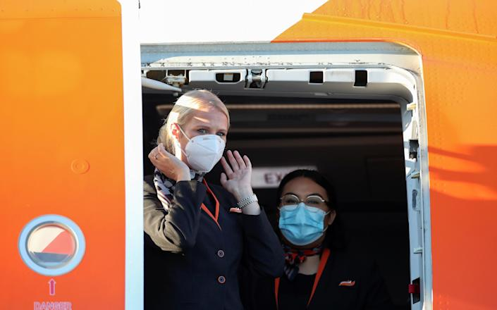 Flight attendants wearing face masks wait for passengers, as EasyJet restarts its operations amid the coronavirus disease (COVID-19) outbreak, at Gatwick Airport, in Gatwick, Britain June 15, 2020. REUTERS/Peter Cziborra