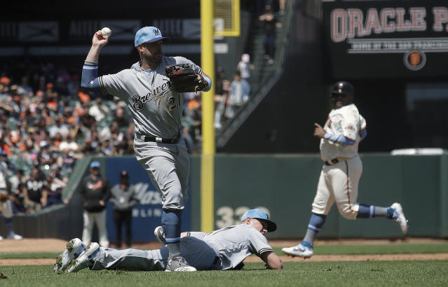 Milwaukee Brewers third baseman Travis Shaw, top left, throws over pitcher Chase Anderson while fielding a bunt by San Francisco Giants' Mike Yastrzemski as Pablo Sandoval, back right, advances to third base during the fifth inning of a baseball game in San Francisco, Sunday, June 16, 2019. Yastrzemski reached first base safely. (AP Photo/Jeff Chiu)
