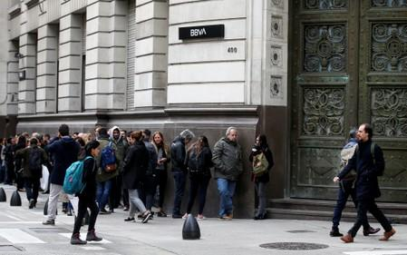 People line up outside BBVA bank before its opening, in Buenos Aires