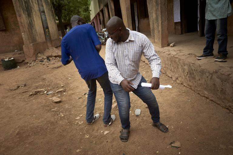 Malian voters greet each other without touching their hands outside a polling booth