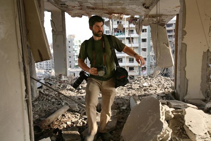 <p>Getty Images photographer Chris Hondros walks the ruins of a building August 21, 2006 in southern Beirut, Lebanon. Hondros, who was on assignment in Misrata, Libya, was killed on April 20, 2011 by a rocket-propelled grenade (RPG). (Photo by Getty Images) </p>